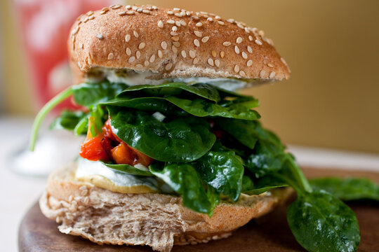 Close up of sandwich with spinach, red pepper and goat cheese