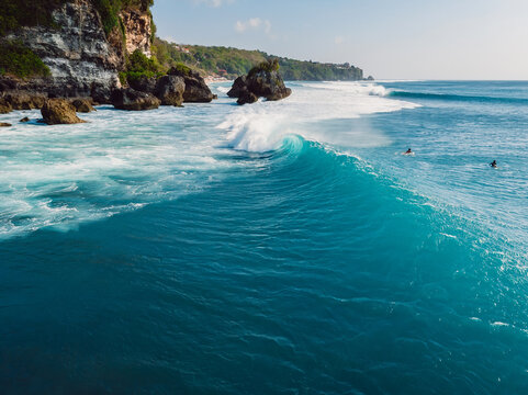 Barrel blue wave in ocean and cliff at background. Aerial view of surfing wave