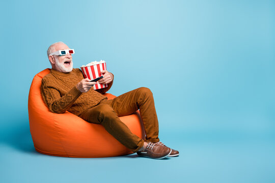 Portrait of his he nice attractive cheerful cheery bearded grey-haired man sitting in bag chair having fun eating corn watching tv comedy isolated over blue pastel color background