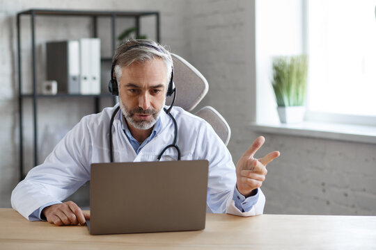 Portrait of senior grey-haired male doctor in his office using laptop for video chat with a patient. Online consultation with doctor for diagnoses and treatment recommendation. Telehealth concept.