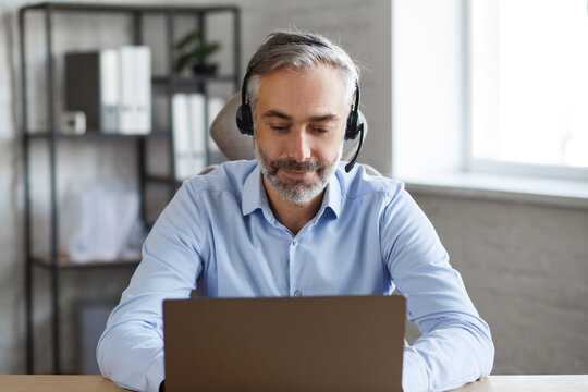Online education, remote working, home education. Portrait of grey-haired senior handsome man teaching online. Online meeting, video call, video conference, courses online.
