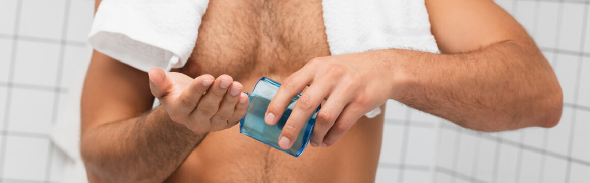 Cropped view of shirtless man with towel pouring after shaving lotion in hand in bathroom, banner