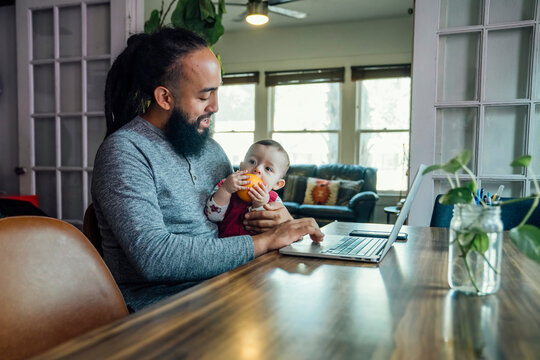 Dad feeding baby while working from home on laptop computer at dining room table
