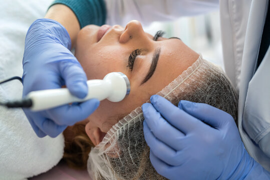 young woman receiving professional procedure facial skin ultrasound cavitation from cosmetologist