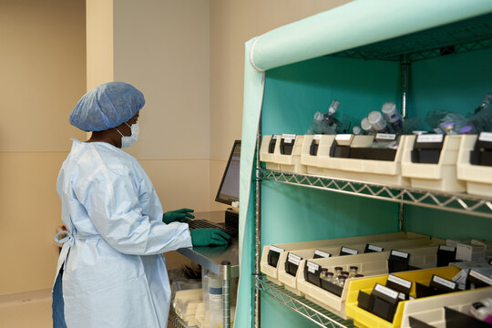 Healthcare worker logging medicines on computer