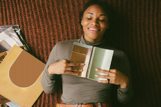 Smiling black woman lying on floor holding book next to stack of vinyl records