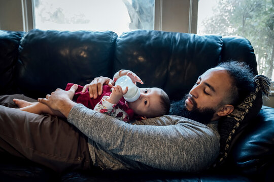 Dad laying on couch with baby laying on his chest feeding from bottle