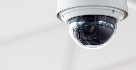 Fototapeta Closeup of white dome type cctv digital security camera installed on ceiling for observation.