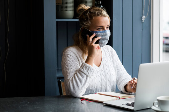 Woman wearing face mask sitting at a cafe table, using mobile phone and laptop, working remotely.