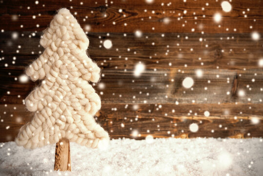 Fabric White Christmas Tree With Snow. Brown Rustic Wooden Background With Snowflakes. Copy Space For Advertisement