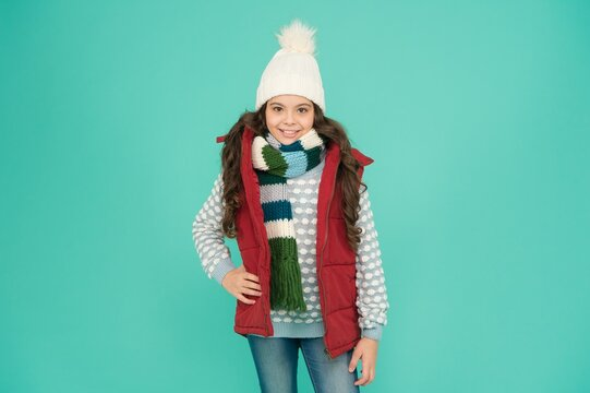 happy teen girl with long curly hair wear puffer waistcoat and knitwear on christmas holidays, winter clothing