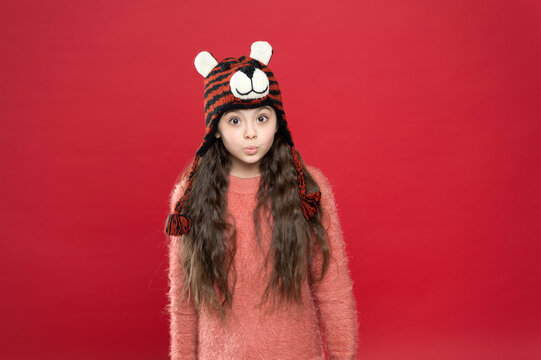 feeling surprised. christmas time activity. holiday fun. cold season accessory. serious child in warm clothing. stylish teen girl with long hair in earflaps. winter kid fashion. happy childhood