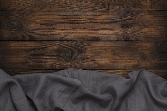 Gray linen cloth on wooden background. Copy space for text.