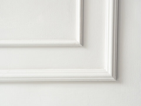 Beautiful ornate white decorative mouldings in studio. Decorative stucco in the classic interior of the house. The angle of the frame molding white for clipart. White cement plaster wall background.