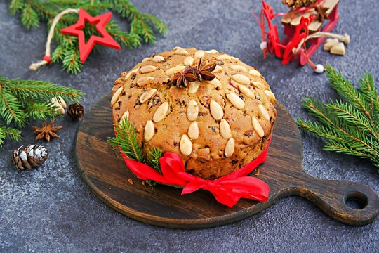 A traditional Scottish Christmas fruit Dundee cake with a mix of dried fruits, decorated with peeled almonds on a wooden board on  a dark concrete background.