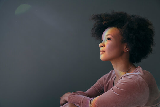 Portrait of young woman with afro looking up into rainbow light