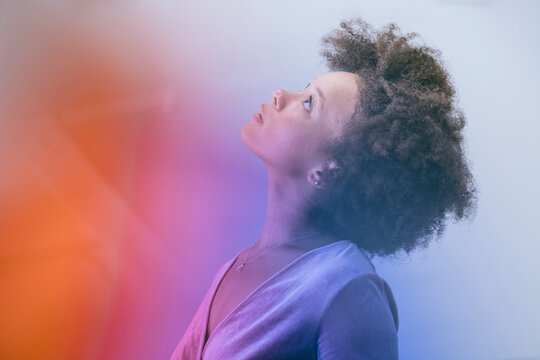 Portrait of woman with afro in multi colored light looking up