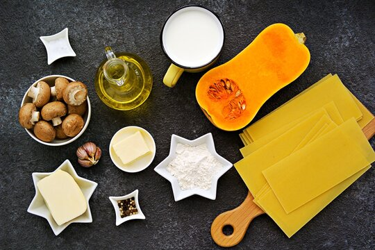 Prepared ingredients for cooking lasagna with pumpkin and mushrooms on an dark concrete background. Lasagna recipes.