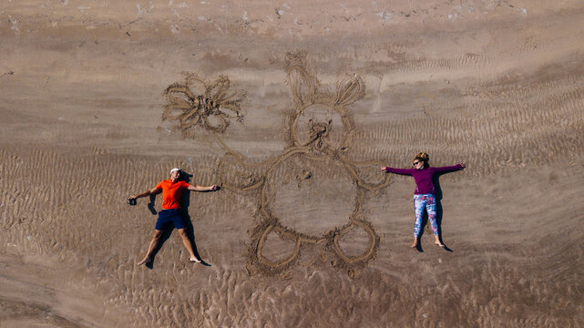 drone selfie of a young couple on the sand laying with a drawn rabbit