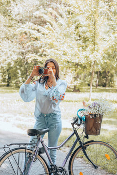 A stylish woman standing near a bicycle while using a retro camera.