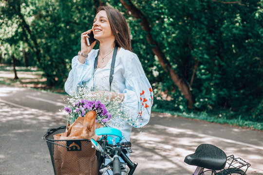 Stylish woman riding a bicycle and using a cellphone.