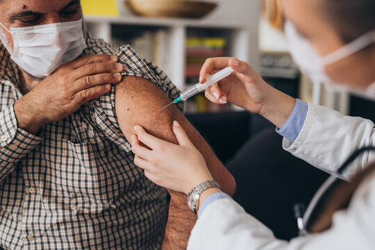 doctor gives corona virus vaccine, home care service concept