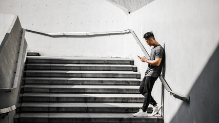 A Chinese Man Stretching With Mobile Phone After A Workout. Fotomurales