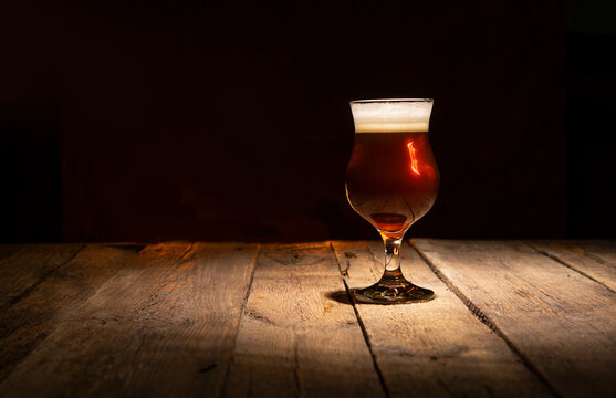 Beer glass on a dark wooden background with copy space. Atmospheric pub mood.