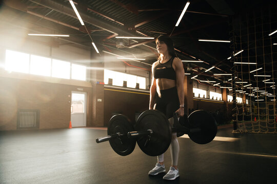 Crossfit athlete - young beautiful woman doing deadlifts with a trap multi grip bar