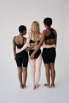 Group of young girls of different races posing in the studio, thin and plus size blondes and brunettes