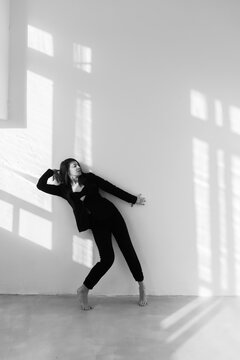 dancing barefooted girl with a back leaned to the wall