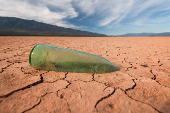 aged glass bottle stuck in the mud as a symbol of drought