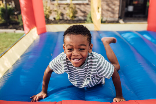 Young boy jumping outdoors in jump house
