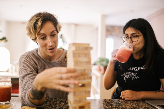 Young women having a drink at home while playing jenga