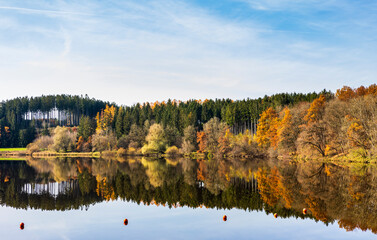 Autumn leaves are reflected in the water of the Windach reservoir in Bavaria
