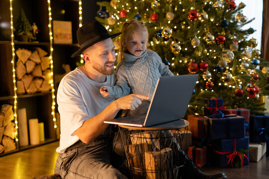 father and daughter playing game on laptop computer. Happy family time - modern lifestyle. Christmas tree with lights on dark red as background.