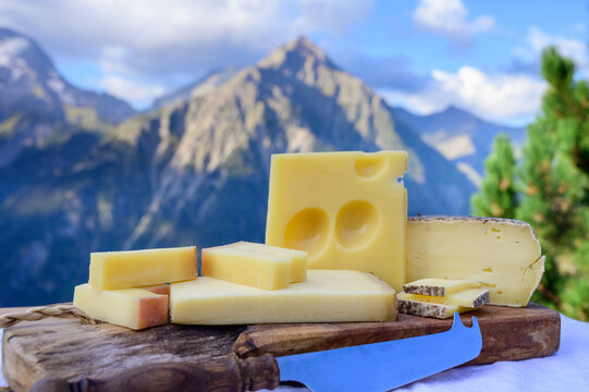 Cheese collection, French beaufort, abondance, emmental, tomme de savoie cheeses served outdoor in Savoy region, with Alpine mountains peaks on background