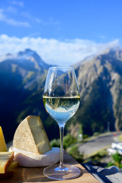 Tasty cheese and wine from Savoy region in France, beaufort, abondance, emmental, tomme and reblochon de savoie cheeses and glass of white wine served outdoor with Alpine mountains peaks on background