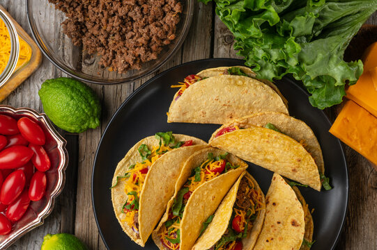 Top view of plate tasty tacos with beef, tomatoes, onion and cheese on ingredients for cooking background. Serving with lime and lettuce. Traditional mexican recipe.