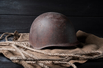 still life soviet helmet and large-caliber cartridge on a black background