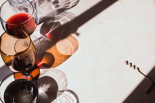 Wine and water glasses with long shadows and wine opener