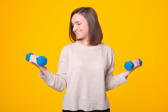 A cheerful young woman is smiling and lifting two blue dumbells .