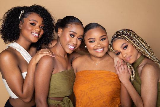 Studio portrait of four happy beautiful black female friends