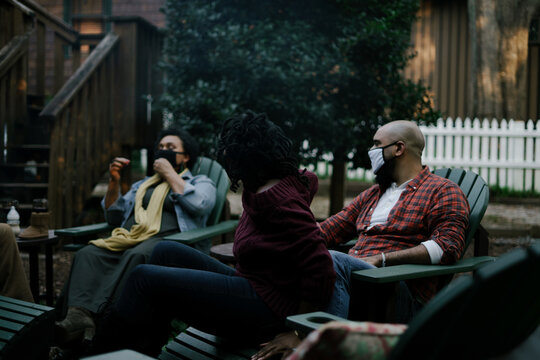 Black friends sitting around firepit safely wearing mask in backyard
