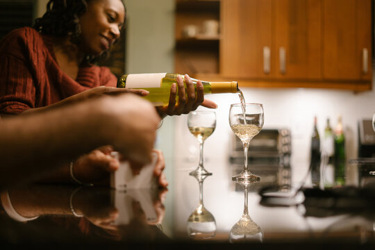 Friend pouring guest wine at house party