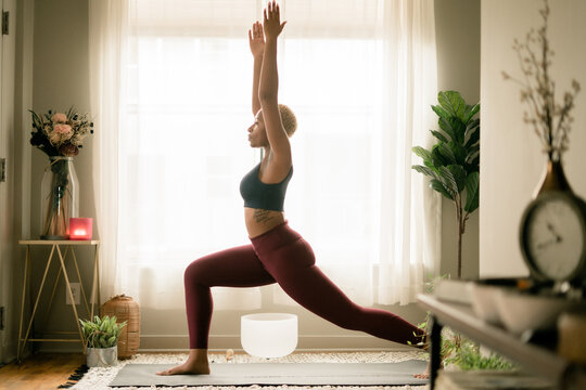 Young woman practices yoga at home