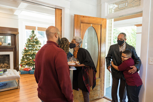 Grandmother and grandfather greet family for Thanksgiving wearing mask