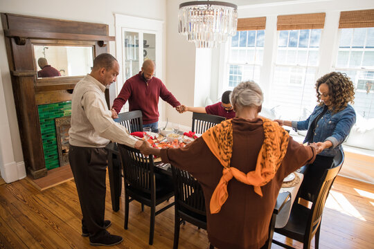 Black multigenerational family praying and blessing the food for Thanksgiving holiday meal