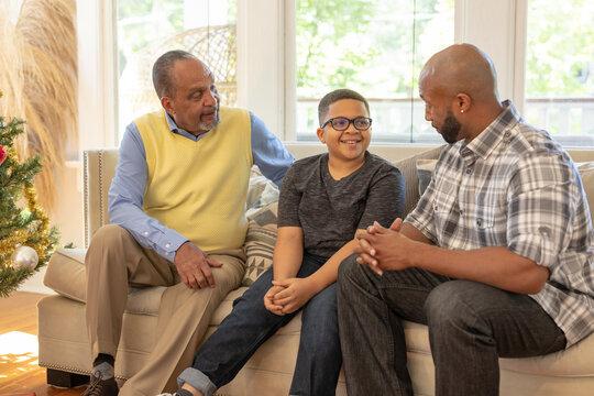Multigenerational black men talking at home during Christmas