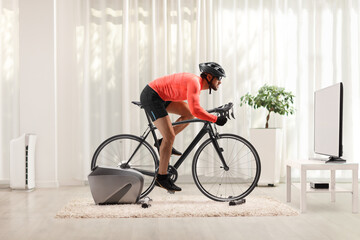 Young fit man cycling with bicycle trainer at home